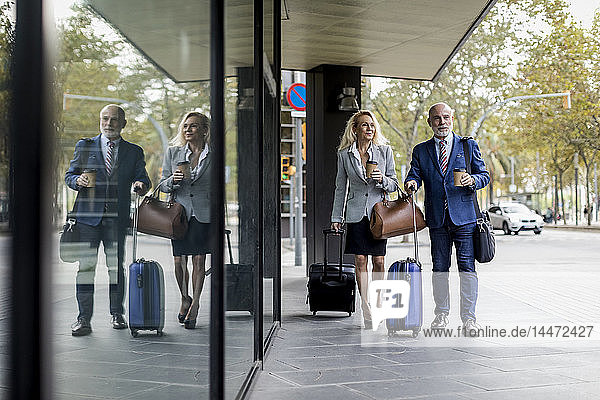 Senior businessman and businesswoman with baggage on the go in the city
