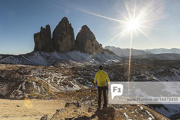 Italien  Tre Cime di Lavaredo  Mann wandert und steht vor den majestätischen drei Gipfeln