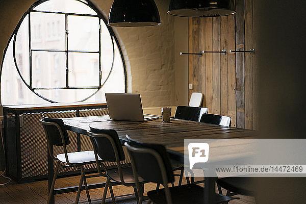 Laptop auf Tisch im hölzernen Konferenzraum