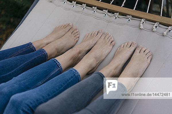 Füße von drei in der Hängematte im Garten liegenden Weibchen