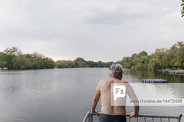 Älterer Mann steht an einem See