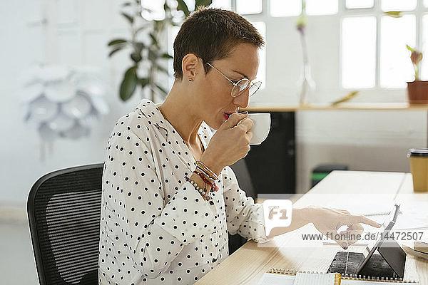 Frau trinkt Kaffee und benutzt Tablette am Schreibtisch im Büro