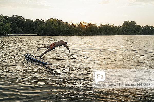 Mann springt bei Sonnenuntergang vom SUP-Brett auf einen See