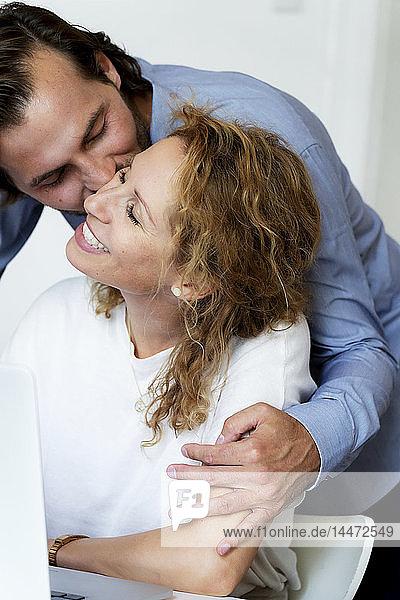 Mann küsst seine lachende Frau