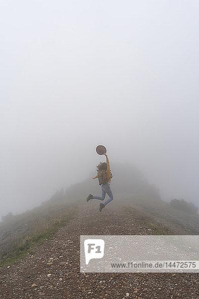 Frau wandert im Nebel  springt auf einen Bergpfad