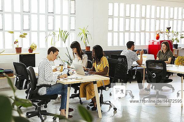 Kollegen,  die am Schreibtisch im Büro arbeiten