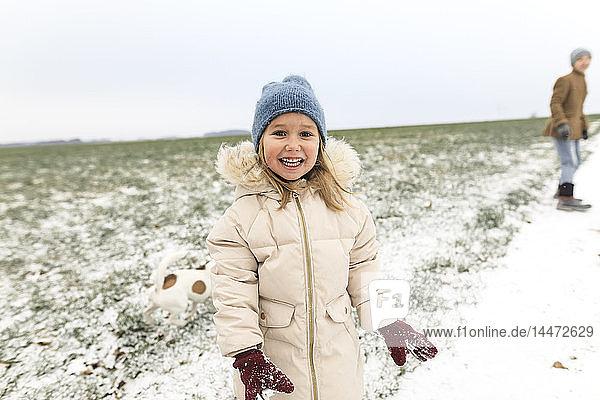Porträt eines glücklichen Mädchens mit Hund und Bruder in Winterlandschaft