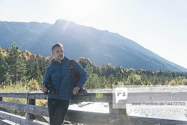 Österreich  Alpen  Mann auf Wanderung mit Fernglas auf einer Brücke stehend