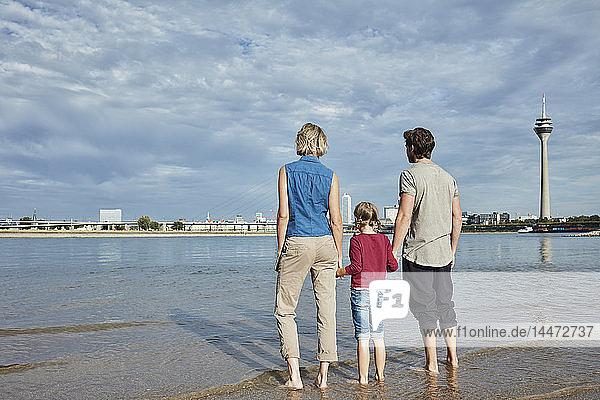 Deutschland  Düsseldorf  Familie mit Tochter am Rheinufer stehend