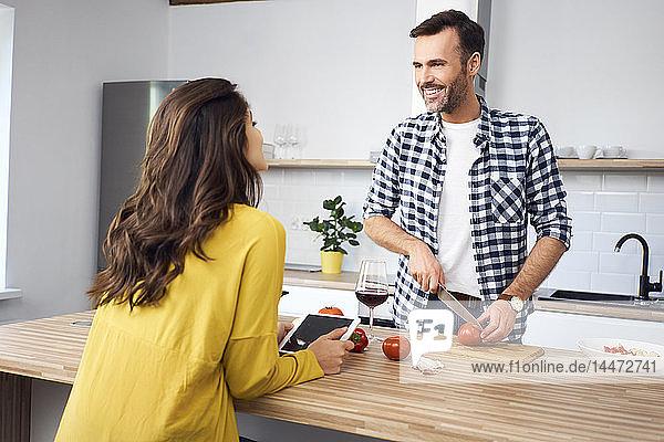 Liebespaar in der Küche  bereitet gemeinsam Spaghetti zu  mit digitalem Tablett