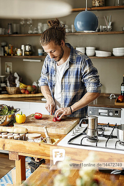Junger Mann bereitet zu Hause Essen zu  schneidet Gemüse in Scheiben