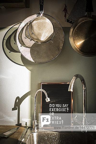 Tafel mit lustigem Text an der Küchenspüle