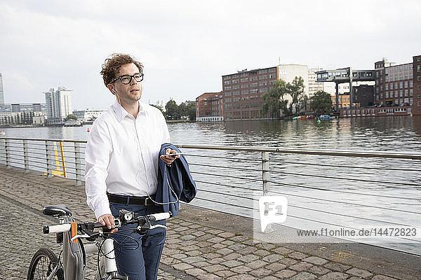 Deutschland  Berlin  Porträt eines Geschäftsmannes mit Smartphone und Kopfhörern beim Schieben seines Fahrrads