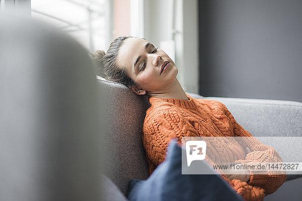 Porträt einer Frau  die einen orangefarbenen Strickpullover trägt und auf der Couch eine Pause macht