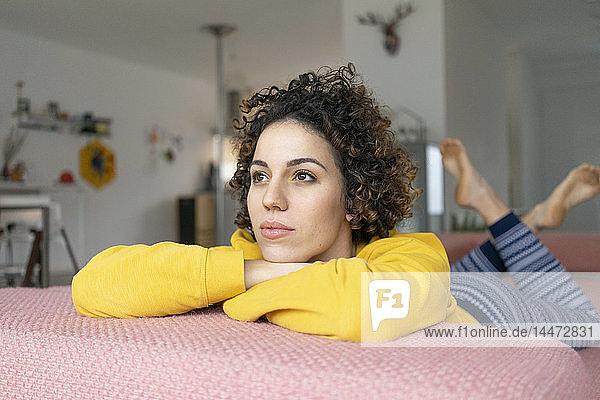 Frau liegt zu Hause auf dem Sofa und denkt nach