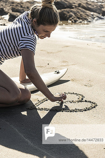 Young woman with surfboard drawing a heart into the sand