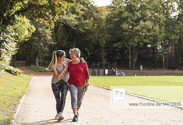 Granddaughter and grandmother having fun  jogging together in the park