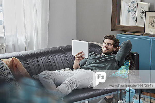 Smiling man with tablet lying on couch at home