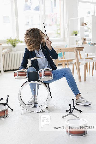 Junge Geschäftsfrau spielt Perkussion