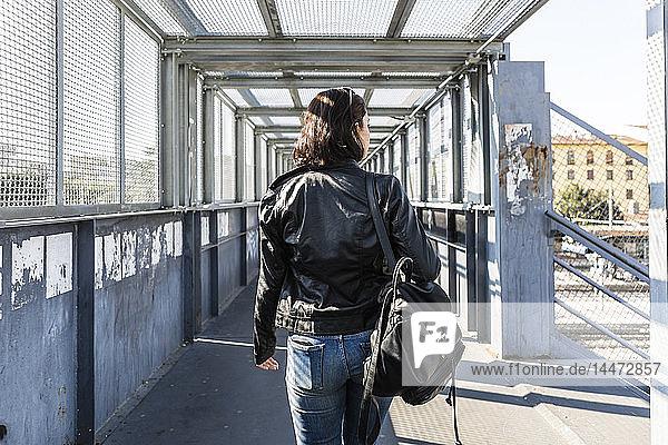 Rückansicht einer jungen Frau  die auf einer Brücke geht