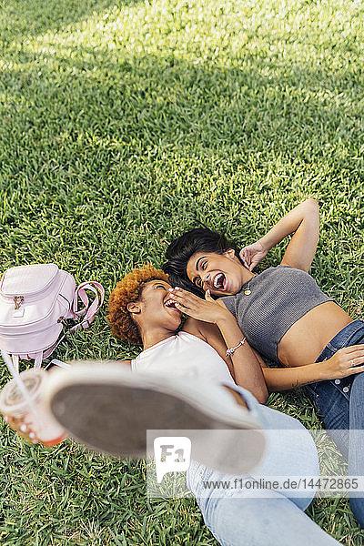 Zwei unbekümmerte Freundinnen entspannen sich in einem Park