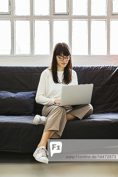 Young woman sitting on couch in office using laptop