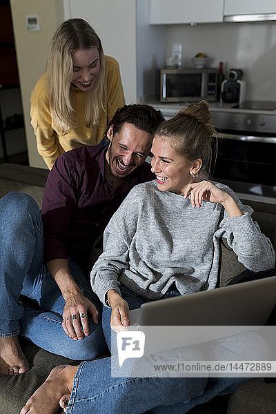 Freunde sitzen auf der Couch im Wohnzimmer  haben Spaß  benutzen Laptop