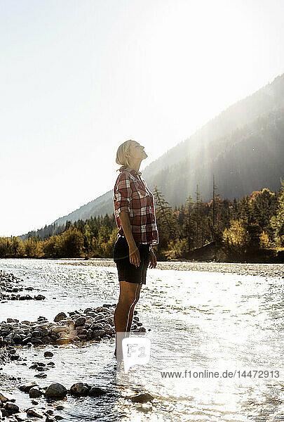 Österreich  Alpen  Frau auf einer Wanderung im Bach stehend