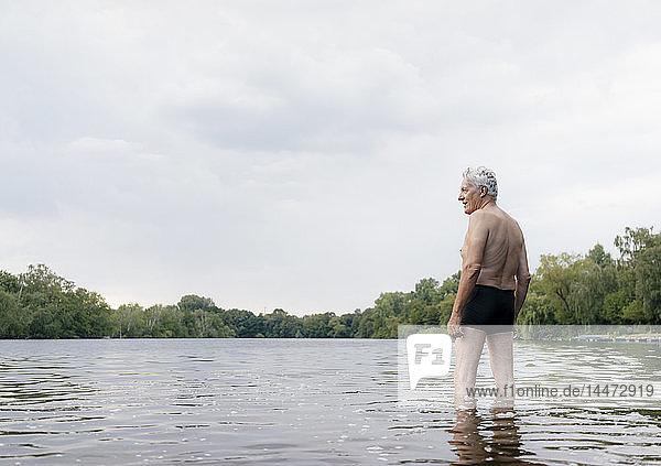 Älterer Mann steht in einem See