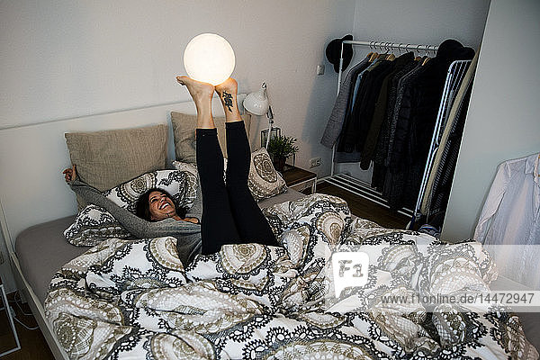 Woman lying on bed  balancing ball-shaped lamp on her feet