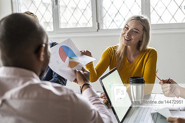 Smiling young businesswoman handing over document in a meeting