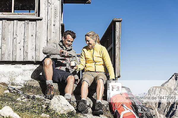 Hiking couple sitting in front of mountain hut  taking a break
