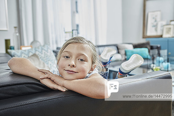 Portrait of confident girl on couch at home