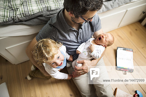Father with his little son and baby daughter at home