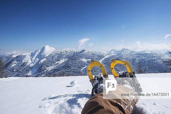 Österreich  Bundesland Salzburg  Altenmarkt-Zauchensee  Mann mit Schneeschuhen im Tiefschnee liegend