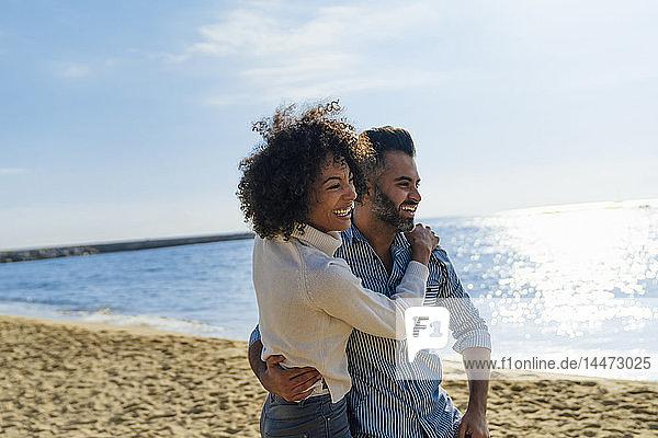 Spain  Barcelona  happy couple hugging on the beach
