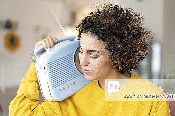 Frau  die zu Hause mit einem tragbaren Radio Musik hört