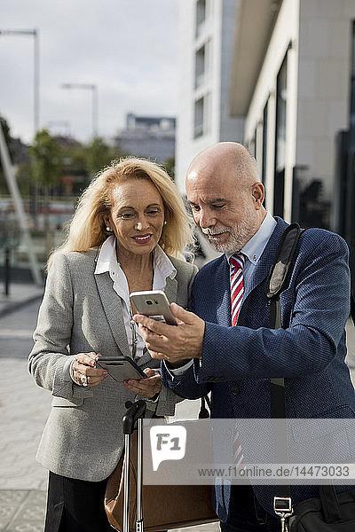Leitender Geschäftsmann und Geschäftsfrau mit Gepäck  die in der Stadt Mobiltelefone benutzen