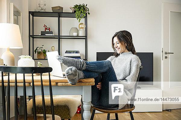 Frau sitzt mit erhobenen Füßen am Tisch und benutzt einen Laptop