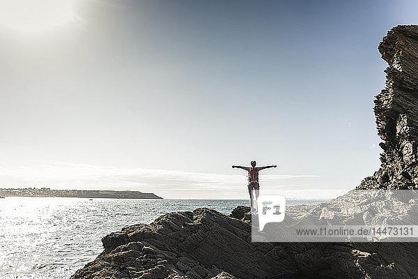 Junge Frau wandert an einem felsigen Strand und schaut sich die Aussicht an