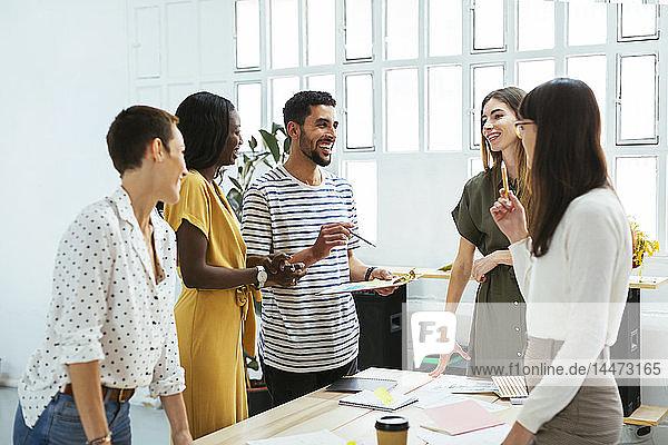 Lächelnde Kollegen arbeiten zusammen am Schreibtisch im Büro und diskutieren über Papiere