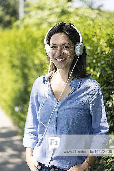 Woman with headphones listening music in nature