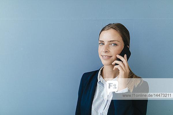 Porträt einer jungen Geschäftsfrau vor blauem Hintergrund  die auf ihrem Smartphone spricht