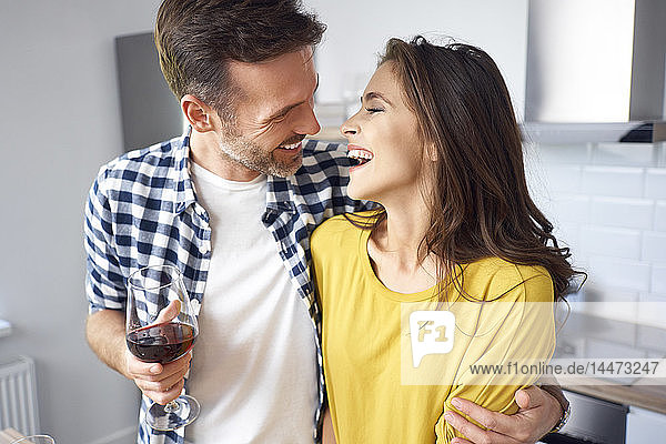 Happy couple standing in kitchen  with arms around  drinking red wine