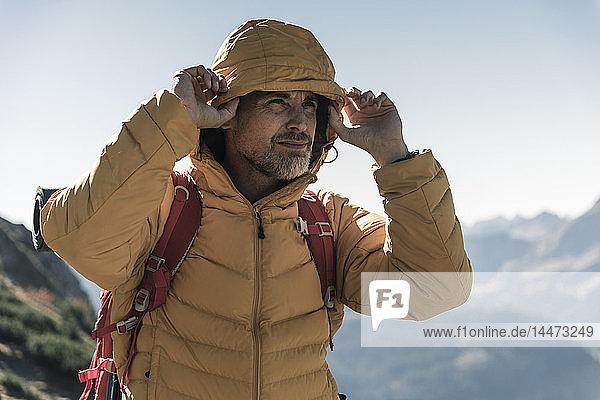Österreich  Tirol  Porträt eines Mannes mit Kapuzenjacke auf einer Wanderung in den Bergen