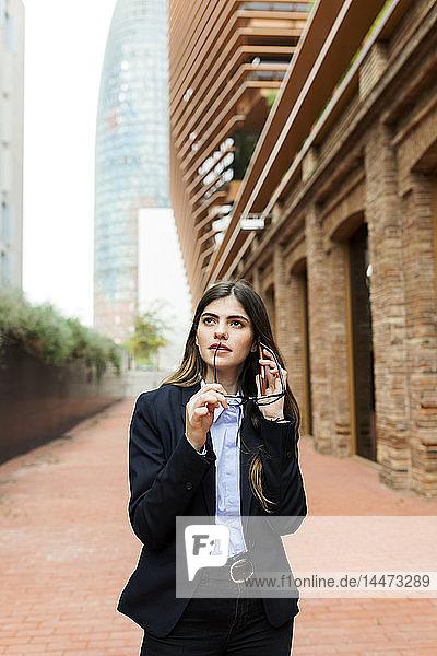 Junge Geschäftsfrau am Handy in der Stadt