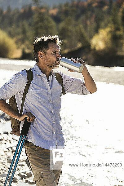 Österreich,  Alpen,  Mann auf Wanderung mit Rast an einem Bach
