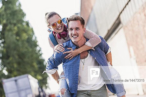 Junger Mann nimmt seine Freundin Huckepack