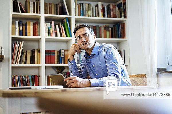 Geschäftsmann mit Tablett am Tisch sitzend mit Bücherregal im Hintergrund