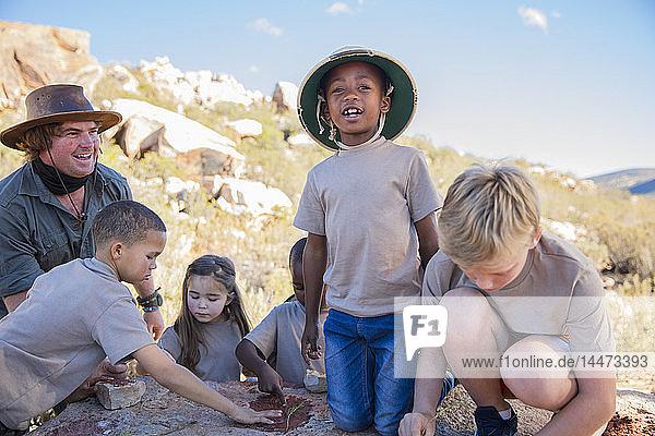 Kinder in einem Camp lernen von einem Führer